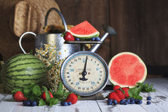 Watermelon Berries on Vintage Scale. A wedge of watermelon, a strawberry and blueberries on weigh platform of vintage kitchen food scale. Whole watermelon and Stock Photos