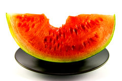 Watermelon with Bite Mark. Slice of watermelon with green skin and red melon with seeds and bite mark on a black plate with a white background stock image