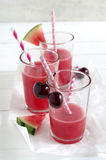 Watermelon-cherry smoothie. Fresh watermelon cherry smoothie in glass with straw Stock Photos