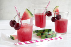 Watermelon-cherry smoothie. Fresh watermelon cherry smoothie in glass with straw Stock Image
