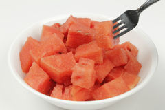 Watermelon Chunks in Bowl with Fork. Organic watermelon pieces in a white bowl with a fork on a white background Royalty Free Stock Photography