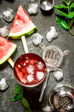 Watermelon cocktail with ice in a shaker. On the stone table stock photo