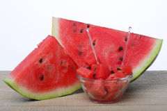 Watermelon. A couple of watermelon slices with a bowl of watermelon cubes Stock Photography