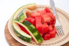 Watermelon cubes and rind of watermelon on a plate.  stock photos