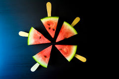 Watermelon cut slice on a stick from ice cream close-up. On a dark blue background Royalty Free Stock Images
