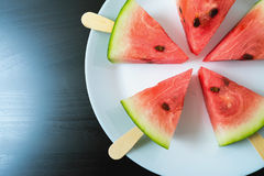 Watermelon cut slice on a stick from ice cream close-up. On white plate Royalty Free Stock Photos