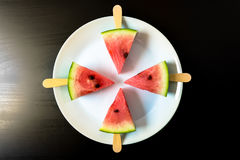 Watermelon cut slice on a stick from ice cream close-up on white plate on a black. Background Royalty Free Stock Photography