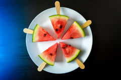 Watermelon cut slice on a stick from ice cream close-up on white plate. On a dark blue background Stock Photography