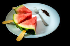 Watermelon cut slice on a stick from ice cream close-up on white plate with fork. On a black background Royalty Free Stock Photos