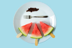 Watermelon cut slice on a stick from ice cream close-up on white plate with fork. On a blue background Stock Images