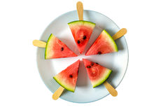 Watermelon cut slice on a stick from ice cream close-up on white plate with fork. On a white background Royalty Free Stock Images