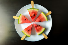 Watermelon cut slice on a stick from ice cream close-up on white plate. On a black background Royalty Free Stock Photos