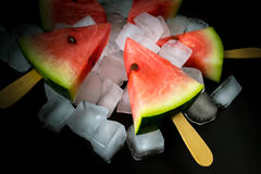 Watermelon cut slice on a stick from ice cream in ice cube close-up. On a black background Royalty Free Stock Photo