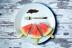 Watermelon cut slice on a stick from ice cream with fork close-up on white plate on an old vintage table. Watermelon cut slice on a stick from ice cream with Stock Image