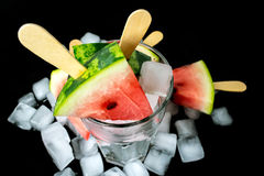 Watermelon cut slice on a stick from ice cream in a glass with ice close-up. On a black background Stock Image