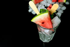 Watermelon cut slice on a stick from ice cream in a glass with ice close-up. On a black background Royalty Free Stock Photos