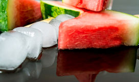 Watermelon cut slice on a stick from ice cream in ice cube close-up with reflection. On dark background Royalty Free Stock Images