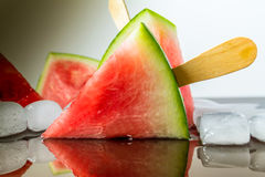 Watermelon cut slice on a stick from ice cream in ice cube close-up with reflection. On dark background Stock Image