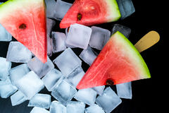 Watermelon cut slice on a stick from ice cream in ice cube close-up. On a black background Stock Photos