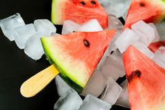 Watermelon cut slice on a stick from ice cream in ice cube close-up. On a black background Stock Photography
