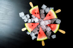Watermelon cut slice on a stick from ice cream in ice cube close-up. On a black background Stock Photo