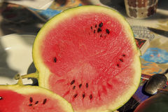 Watermelon cut into the table. Ripe juicy watermelon cut into the table with black stones Royalty Free Stock Photos