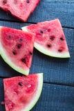 Watermelon  on a dark wooden background, top view. Juicy, sweet slices of watermelon  on a dark wooden background, top view Royalty Free Stock Photo