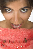 Watermelon desire. Beautiful young woman eating a slice of watermelon Stock Photography