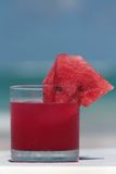 Watermelon drink. Served in glass on the beach with sea in background Stock Photo