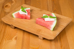 Watermelon with feta cheese and mint. On a wooden surface Stock Images