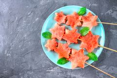 Watermelon in the form of stars on skewers with leaves of mint lies on a plate. The blue dish is like a rocket in space. Top view. Royalty Free Stock Image