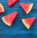 Watermelon fruit pieces  on a  blue rustic wood background, flat Royalty Free Stock Images