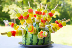 Watermelon and fruit skewers. Watermelon decorated with colorful fruit skewers, with shallow depth of field Royalty Free Stock Photo