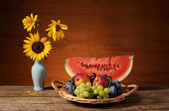 Watermelon, fruit and sunflowers in a vase Royalty Free Stock Photos