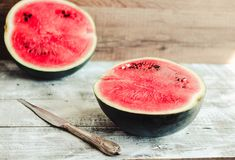 Watermelon fruit in a wooden background. Antioxidant summer food. Watermelon and pieces of fruit in a wooden background. Antioxidant summer food.Minimalism stock photos