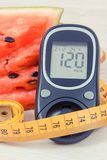 Watermelon, glucometer with result sugar level and tape measure, healthy lifestyles and slimming concept Royalty Free Stock Photo
