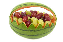 Watermelon and Grapes. Grapes in a watermelon basket Royalty Free Stock Photo