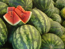 Watermelon heap at the marketplace. Heap of watermelons for sale, with one of them slashed to see the ripe pulp stock photography