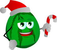 Watermelon holding a candy cane and wearing Santa's hat Royalty Free Stock Photography
