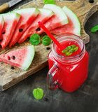 Watermelon juice and pieces of watermelon on a dark wooden background, rustic style Stock Image