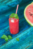 Watermelon juice. Resh watermelon juice with mint in a jar with a straw on a blue wooden table Stock Images