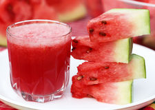 Watermelon juice with sliced fruit on white plate Royalty Free Stock Photos