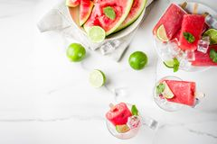 Watermelon and lime popsicles. Sweet summer watermelon and lime popsicles with sliced watermelon and mint, on white marble background copy space royalty free stock photo