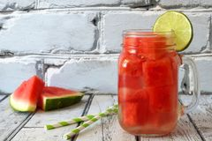 Watermelon lime water in mason jar against white wood, bricks Stock Photos