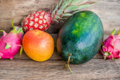 Watermelon, mango, pineapple, dragon fruit on the old wooden background Stock Photo