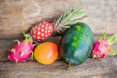 Watermelon, mango, pineapple, dragon fruit on the old wooden background Stock Image