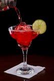 Watermelon margarita. Pouring a watermelon margarita over ice on a dark bar Stock Image