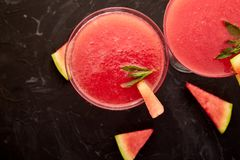 Watermelon margarita cocktail Fresh watermelon lemonade summer drink. Watermelon margarita cocktail on black background. Fresh watermelon lemonade with mint and royalty free stock image