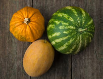 Watermelon, melon and pumpkin on old wooden table. Royalty Free Stock Photography