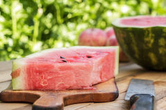 Watermelon and old knife on the table Stock Photos